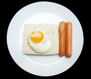 用早餐用鸡蛋煎的,面包和香肠在白色盘 库存图片