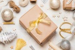 用明亮的金黄弓和各种各样的圣诞节装饰装饰的圣诞节或新年礼物盒在它附近 圣诞节新年度 免版税库存图片
