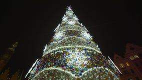 用明亮的闪耀的诗歌选和玩具装饰的美丽的圣诞树在城市广场为假日反对夜空 股票视频