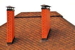 用有两个砖烟囱的红色瓦片盖的屋顶 库存照片
