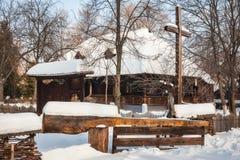用木材建造在雪盖的村庄在村庄博物馆,布加勒斯特 免版税库存照片