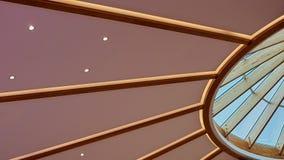 用木材建造形成一扇圆天窗的屋顶的射线 图库摄影