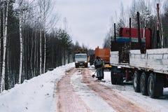 用木材建造用日志装载的卡车驾驶雪道 免版税图库摄影