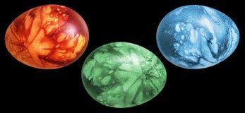 用杂草叶子版本记录手画和装饰的三个红色被洗染的五颜六色的复活节彩蛋隔绝在黑背景 库存照片