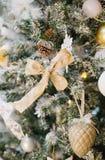 用杉木锥体、丝带和球装饰的圣诞树 库存照片