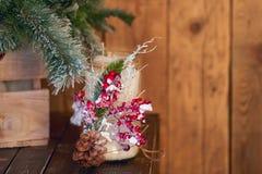 用杉木锥体和红色ashberry下面圣诞树装饰的白色蜡烛台在木背景 库存照片