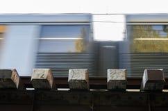 用栏杆围运行在快动作,特写镜头图片的轨道的火车 库存图片