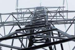 用树冰盖的高压传输塔的特写镜头大气照片站立在灰色天空 免版税库存照片