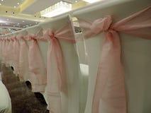 用桃红色弓装饰的白色椅子行  库存图片