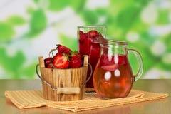 用桶提草莓,玻璃,有饮料的,在抽象绿色的抹水罐 免版税库存照片