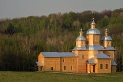 用森林盖的小山的背景的木东正教 在日落 免版税库存图片
