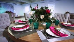 用植物布置装饰的一张圆的木桌做由有附近有的桃红色餐巾的白色板材在 股票录像