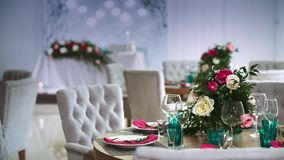 用植物布置装饰的一张圆的木桌做由有附近有的桃红色餐巾的白色板材在 股票视频