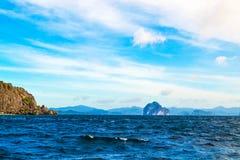 用植物盖的蓝色海、海峭壁和明亮的蓝天的美妙的看法 El Nido巴拉望岛菲律宾 图库摄影