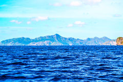 用植物盖的蓝色海、海峭壁和明亮的蓝天的美妙的看法 El Nido巴拉望岛菲律宾 免版税库存图片