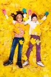 用槭树橙色叶子盖的两个愉快的女孩 免版税图库摄影