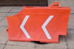 用橙色塑料结构盖的残破的阴沟用于 免版税库存照片