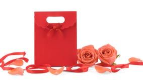 用橙色玫瑰和瓣装饰的红色礼物袋子 免版税库存照片