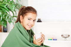 用毯子在家包括的妇女饮用的茶 库存照片