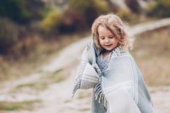 用毯子报道的女孩逗留在公园 免版税图库摄影
