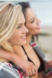 用毯子盖的两个少妇在海滩 免版税库存照片