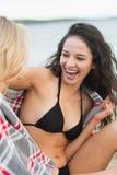用毯子盖的两名快乐的妇女在海滩 免版税图库摄影
