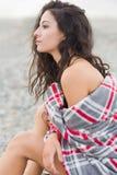 用毯子盖的严肃的妇女在海滩 免版税库存照片
