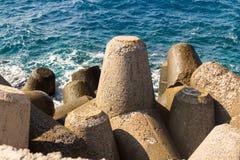 用水泥涂块保护岸的三角水坝免受波浪 免版税库存照片