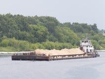 用沙子浮游物装载的驳船 免版税库存图片