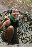 用泥盖的微笑的妇女爬行在伪装网下 免版税库存图片