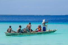 用浆划一条木小船的五位渔夫 免版税库存照片