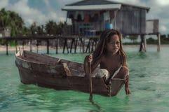 用浆划一条木小船的小女孩 库存图片