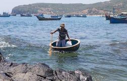 用浆划一条竹圆的小船的越南渔夫 库存图片