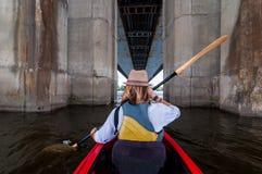 用浆划一艘皮船的妇女在桥梁支持之间的河 划皮船在城市 都市夏天冒险概念 免版税库存照片