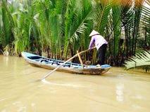 用浆划在一条小船的越南妇女 免版税库存图片