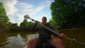 用浆划在河的年轻人独木舟 行动照相机,慢动作 影视素材