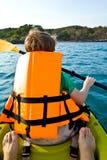 用浆划在独木舟的男孩在 免版税库存照片