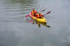 用浆划在皮船的两个伙计 图库摄影