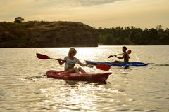 用浆划在美丽的河或湖的朋友皮船在剧烈的晚上天空下在日落 库存图片
