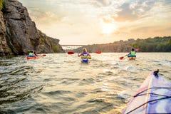 用浆划在美丽的河或湖的朋友皮船在高岩石附近在剧烈的晚上天空下在日落 免版税库存照片