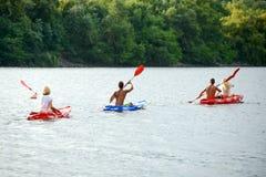 用浆划在美丽的河或湖的朋友皮船晚上 免版税库存图片
