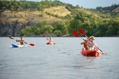 用浆划在美丽的河或湖的朋友皮船晚上 免版税库存照片