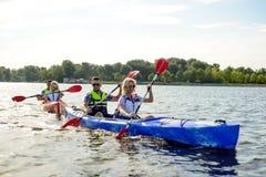 用浆划在美丽的河或湖的朋友皮船 免版税图库摄影