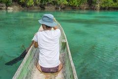 用浆划在蓝色盐水湖的传统木独木舟的游人在遥远的Togean海岛,中央苏拉威西岛,印度尼西亚 免版税库存图片