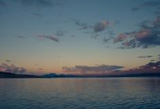 用浆划在镇静Akkajaure湖的遥远的皮艇 图库摄影