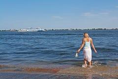 用浆划她的赤脚的白肤金发的妇女在一次洪水期间在伏尔加河的背景中有小船的 免版税库存照片