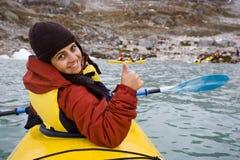 用浆划妇女黄色年轻人的皮船 免版税库存照片