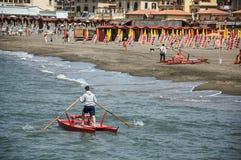 用浆划救助艇的人概要在Ostia附近海滩  免版税库存照片