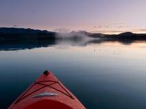 用浆划日落水的镇静皮船 库存图片