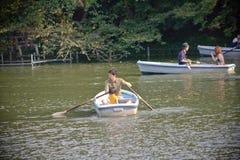 用浆划有家庭的一条小船在公园 免版税库存照片